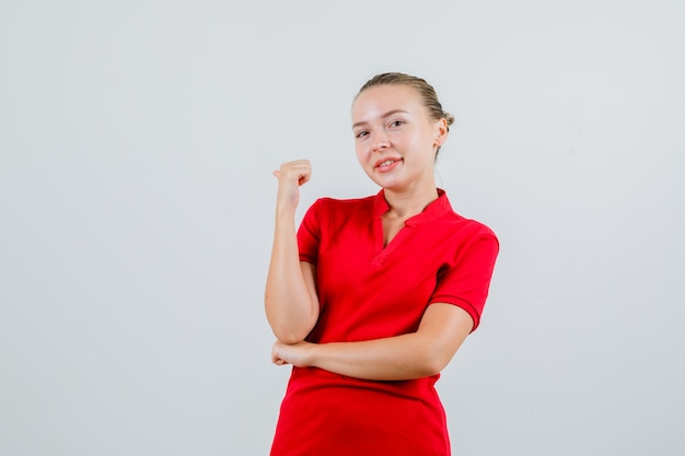 Young woman in red t-shirt pointing back with thumb and looking merry