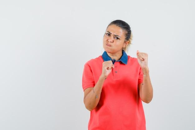 Giovane donna in maglietta rossa in piedi in posa boxer e guance gonfie e potente, vista frontale.