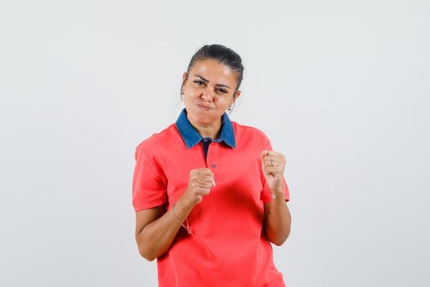Giovane donna in maglietta rossa in piedi nella posa del pugile e guance gonfie e sembra carina, vista frontale.