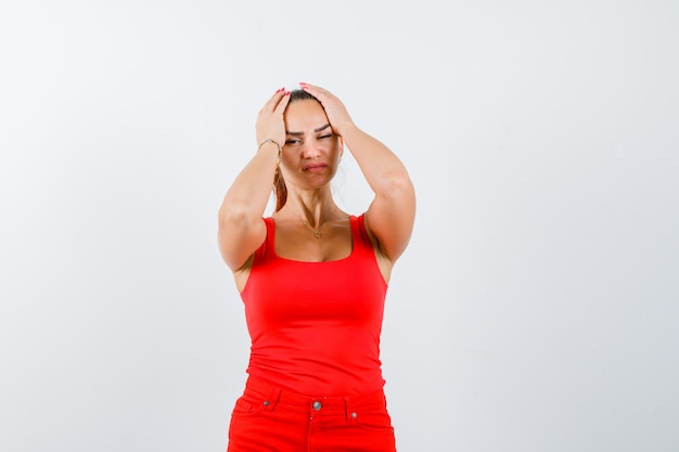 Young woman in red tank top, pants holding head with hands and looking upset , front view.