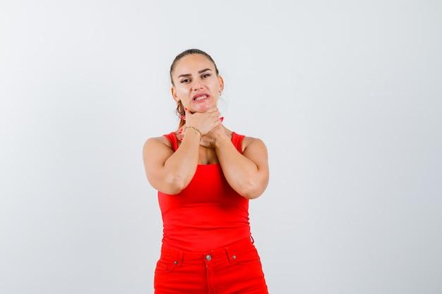 Giovane donna in canottiera rossa, pantaloni che le tengono la gola con le mani e che sembra delusa, vista frontale.