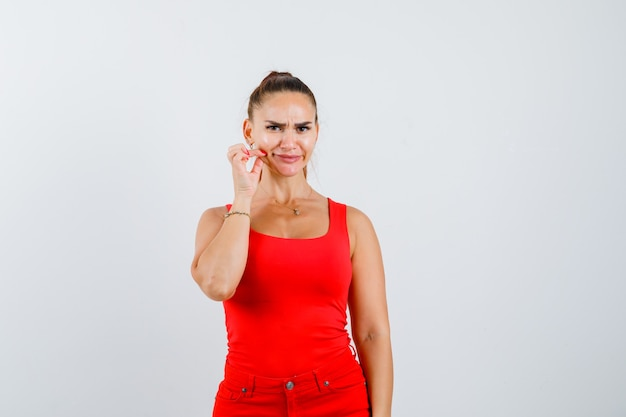 Young woman in red tank top, pants palping cheeks with fingers and looking dissatisfied , front view.