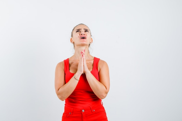 Young woman in red tank top, pants showing namaste gesture and looking troubled , front view.