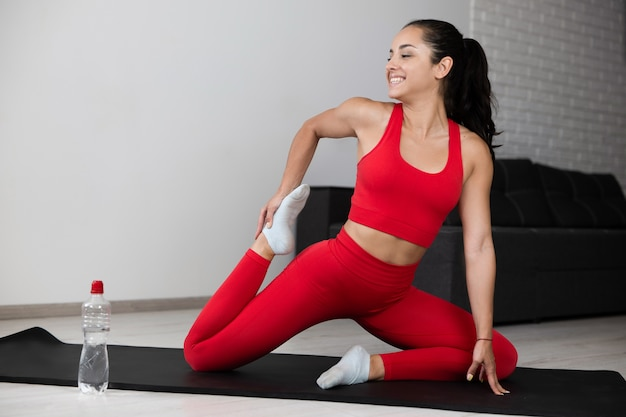Young woman in red tracksuit doing exercise or yoga at home. cheerful positive happy sporty girl stretching up her legs during warming up exercises. holding one leg close to her booty. home training.