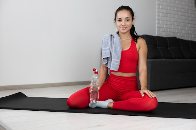 Young woman in red tracksuit doing exercise or yoga at home. confident positive sporty well-built modelhold water bottle in hand and towel on shoulder. advertisement. sport life balance.
