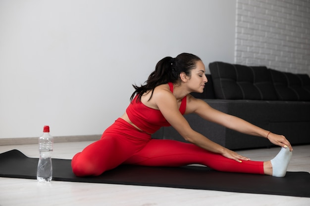 Young woman in red tracksuit doing exercise or yoga at home. well-built strong sporty girl stretching her left leg and warming up before starting to exercise. training alone in apartment on mat.