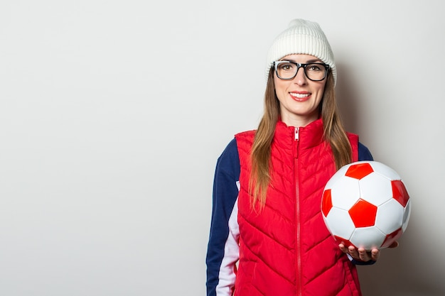 Young woman in a red vest, hat and glasses holds a soccer ball against a light wall