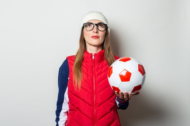 Young woman in a red vest, hat and glasses holds a soccer ball and looks up against a light wall
