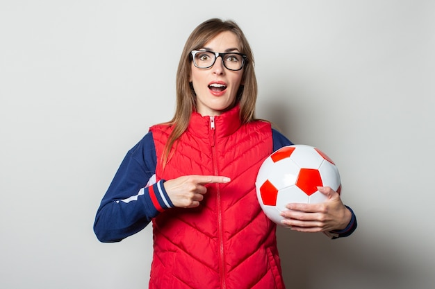 Young woman in a red vest holds a soccer ball in her hands and points at it with her finger