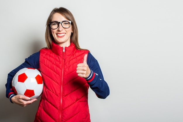 Young woman in a red vest holds a soccer ball in her hands and shows a gesture