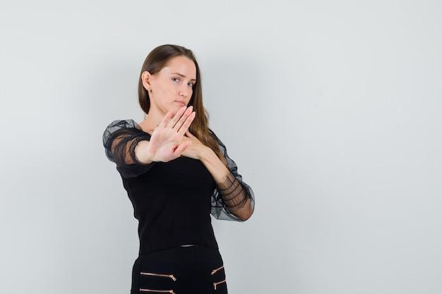 Молодая женщина отказывается от чего-то в черной блузке и выглядит неохотно Бесплатные Фотографии
