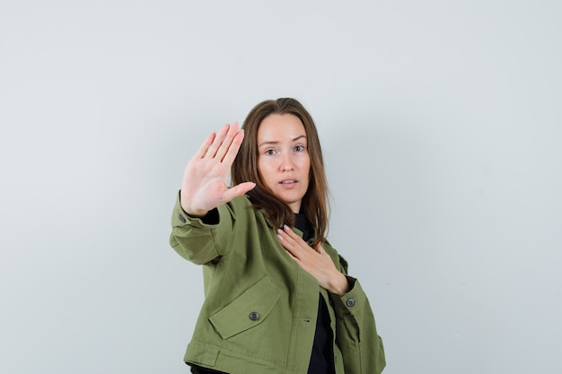 緑のジャケットで手振りで何かを拒否し、注意深く見ている若い女性。正面図。
