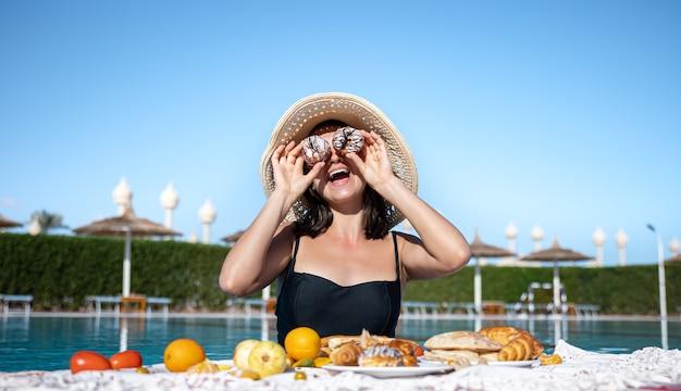 Молодая женщина радуется вкусной еде у бассейна