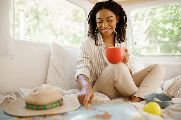 젊은 여자는 트레일러에서 캠핑, 침대에서 휴식. 커플은 밴, 캠핑카 휴가, 캠핑카 캠핑 레저