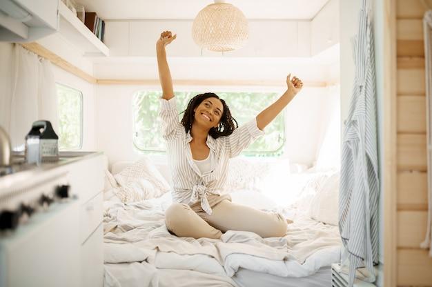 젊은 여자는 트레일러에서 캠핑, 침실에서 휴식을 취하십시오. 커플은 밴, 캠핑카 휴가, 캠핑카 캠핑 레저