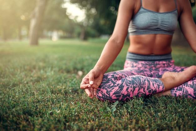 Молодая женщина расслабиться в позе йоги на траве