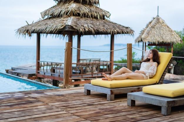若い女性は海の背景とプールのデッキチェアでリラックス