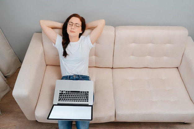 Young woman relaxes sitting on the sofa in the living room after doing work on a laptop concept of a...