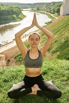 Young woman relaxes in a yoga pose on nature in a park