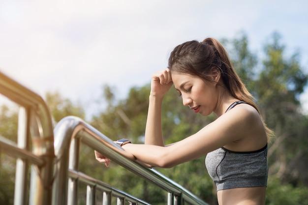 그녀의 몸을 신선하게하는 공원에서 울타리에 조깅 운동 후 휴식 젊은 여자