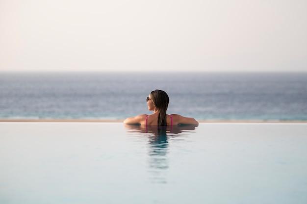 Giovane donna che si rilassa da sola in piscina