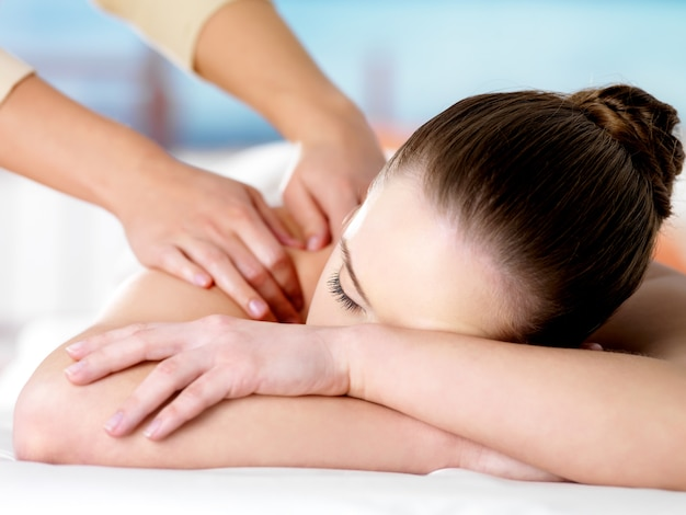 Young woman relaxing in beauty salon and getting shoulder massage - colored space