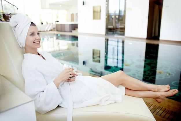 Молодая женщина отдыхает у бассейна в спа