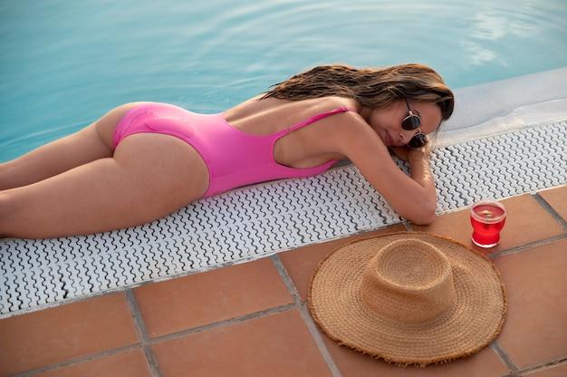 プールサイドでリラックスした若い女性