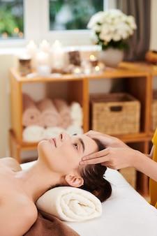 치료사가 그녀의 얼굴을 마사지하는 동안 스파 절차 중 휴식을 취하는 젊은 여성