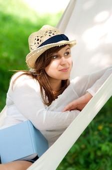 Young woman relaxing in a hammock with book