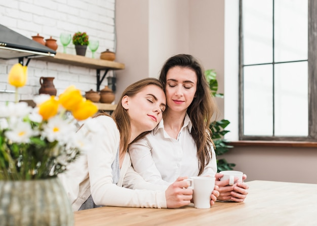Young woman relaxing on her girlfriend's shoulder holding cup of coffee in hand