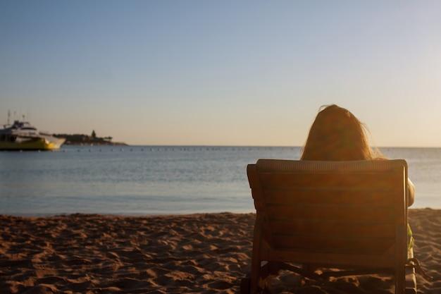朝、ビーチのデッキチェアでリラックスし、夜明けに会う若い女性。