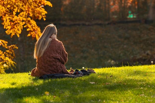 カメラに背を向けて水を見下ろす芝生の土手に座って秋または秋に公園でリラックスした若い女性