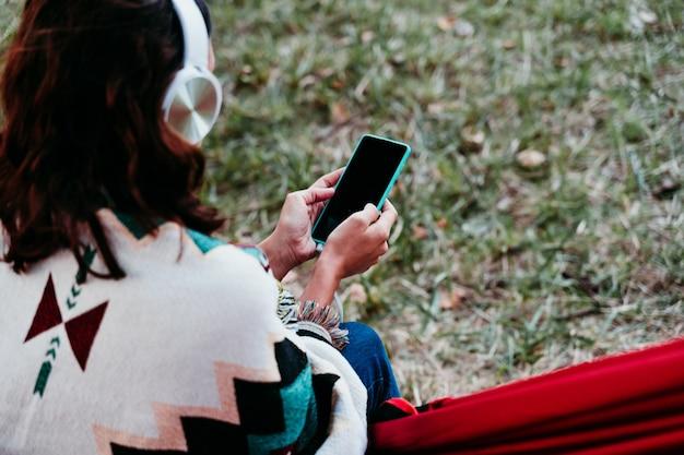 Молодая женщина расслабляется в гамаке во время прослушивания музыки