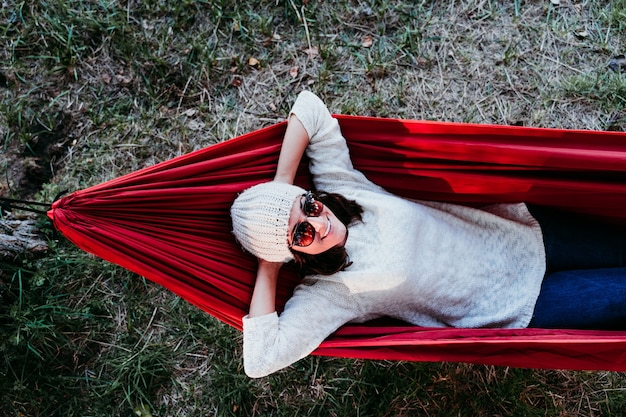 Молодая женщина, расслабляющаяся в гамаке
