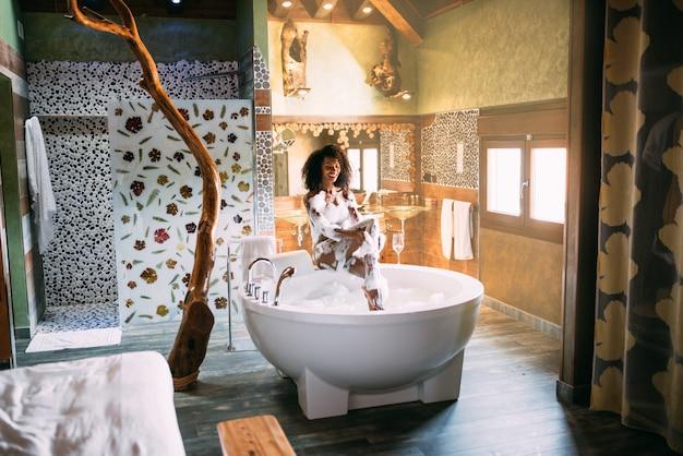 Молодая женщина, расслабиться в гидромассажной ванне в пене