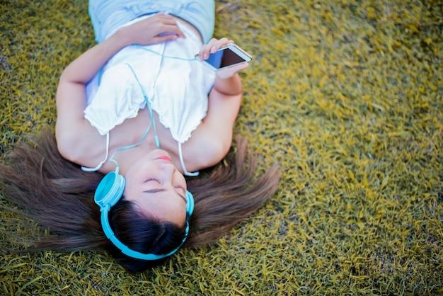 자연 공원에서 편안한 젊은 여자. 정원에서 여름에 휴가입니다.