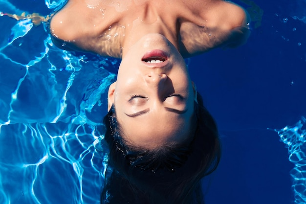 Молодая женщина, расслабляющаяся в бассейне
