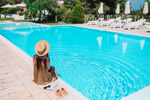 Young woman relaxing at a luxury hotel pool