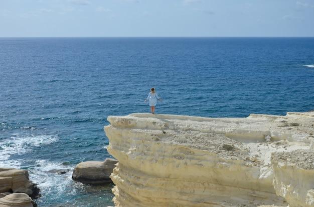 若い女性は崖でリラックスし、彼女の自由と新鮮な空気を楽しんでいます