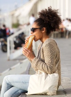 Young woman relaxing outdoors and eating food