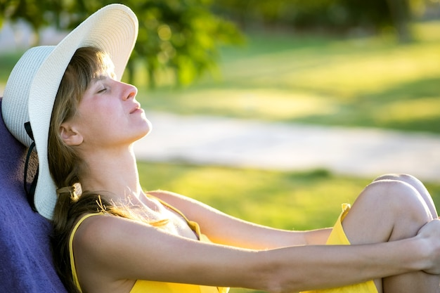 Молодая женщина расслабляющий на открытом воздухе в солнечный летний день. счастливая дама, лежа на удобном шезлонге, мечтательное мышление. спокойная красивая улыбающаяся девушка, наслаждаясь свежим воздухом, расслабляясь с закрытыми глазами.