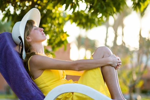 Молодая женщина отдыха на открытом воздухе в солнечный летний день. счастливая дама лежа на удобном шезлонге мечтает думать. спокойная красивая улыбающаяся девочка, наслаждающаяся свежим воздухом, расслабляющимся с закрытыми глазами.