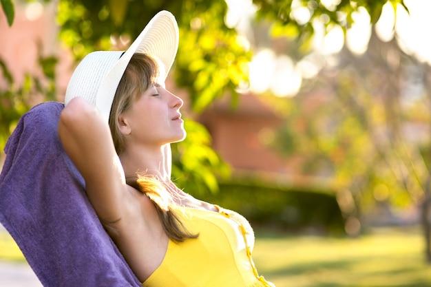 Молодая женщина отдыхает на открытом воздухе в солнечный летний день