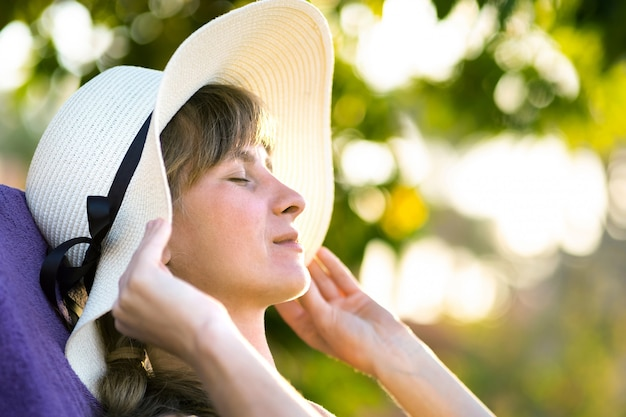 Young woman relaxing outdoors on sunny summer day. happy lady lying down on comfortable beach chair daydreaming thinking. calm beautiful smiling girl enjoying fresh air relaxing with closed eyes.