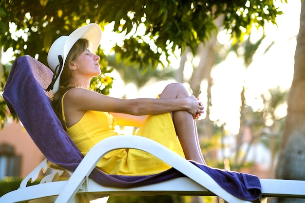 Young woman relaxing outdoors on sunny summer day.