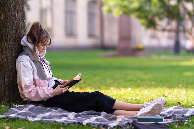 Молодая женщина расслабляется, читая книгу или учится под тенистым деревом в парке или саду, крупным планом, сбоку