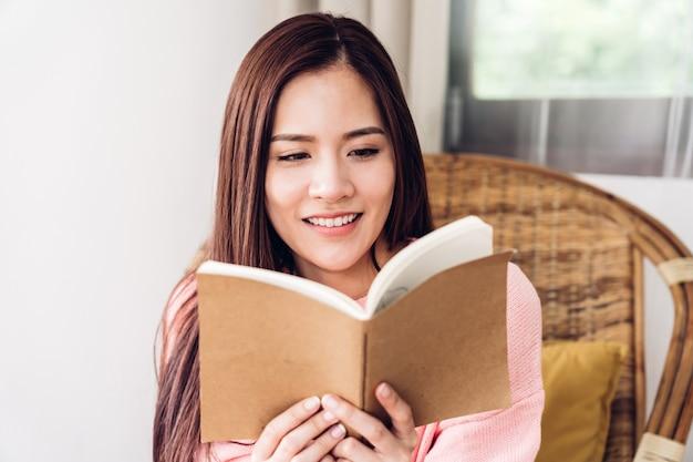 若い女性が自宅のベッドで本を読んでリラックス