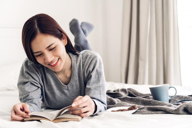Молодая женщина расслабляющий и читать книгу на кровати у себя дома Premium Фотографии