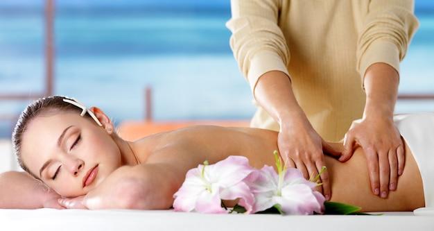 Giovane donna che si distende nel salone della stazione termale e che ottiene massaggio del corpo